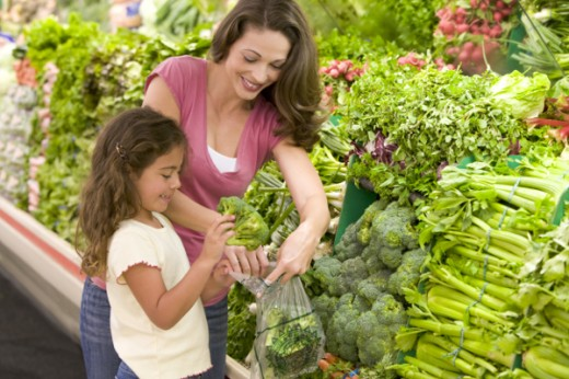 Mother and daughter shopping for produce in supermarket