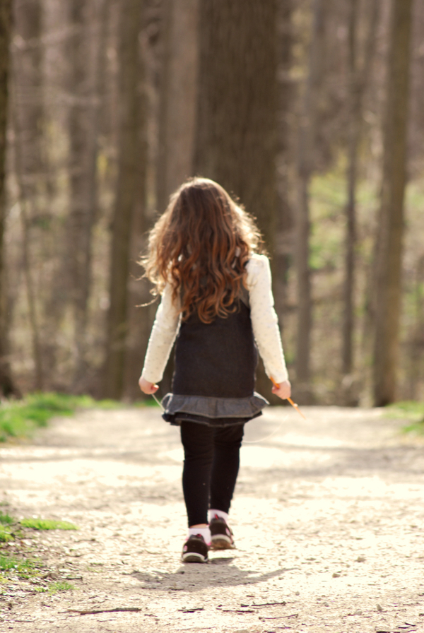 A little girl walking in the woods